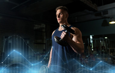 young man with dumbbells exercising in gym