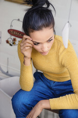 Woman in contemplative mood wearing jeans and top, nostalgic mood.