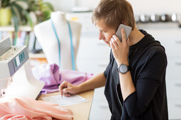 fashion designer calling on smartphone at studio