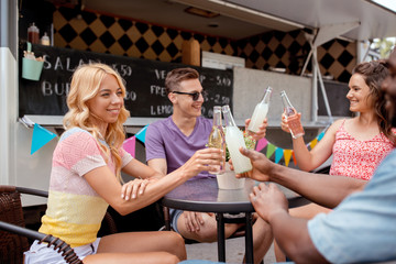 friends clinking bottles with drinks at food truck