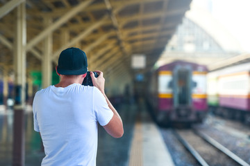Man take a picture in train station with a camera
