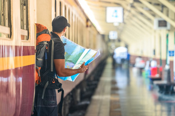 Man with a world map in a train station in asian city, Bangkok, Thailand