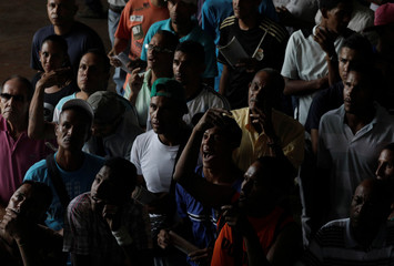 Gamblers react as they watch a horse race in La Rinconada Hippodrome in Caracas