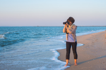 Woman photographer takes a picture on the seashore