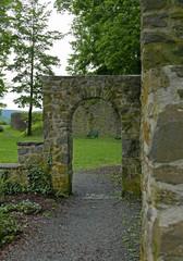 Gemauerter Bogen in einem Park als Teil einer Burgruine