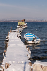 Beautiful lake winter scene with an old wooden pier and a fishing boat. The boat in snow at the lake in the winter