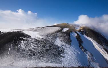 Panorama del Cratere del  Vulcano Etna  in Sicilia con neve ed emissioni vapore e fumo