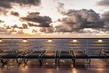 Sunbeds on cruise ship with cloudy sky