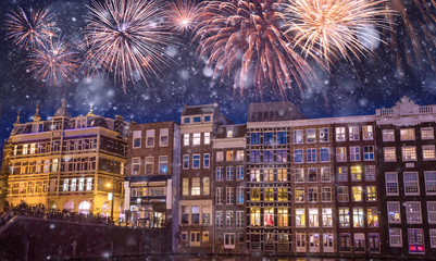 Traditional old buildings and boats at night with fireworks on the black sky in Amsterdam, Netherlands