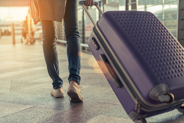 Traveler with suitcase in airport concept.Young girl  walking with carrying luggage and passenger for tour travel booking ticket flight at international vacation time in holiday rest and relaxation. Fototapete