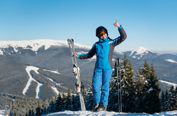 Full length shot of a cheerful woman skier showing thumbs up on top of a mountain with her skis at ski resort, smiling joyfully incredible winter scenery on the background copyspace