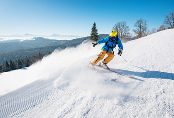Professional male skier riding the slope on a beautiful winter day copyspace ski resort travelling tourism vacation extreme adrenaline