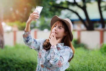 Pretty asian girl in vintage dress taking a selfie in park.