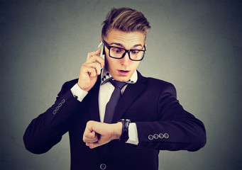 Business and time management concept. Businessman looking at wrist watch, talking on mobile phone running late for meeting. Time is money