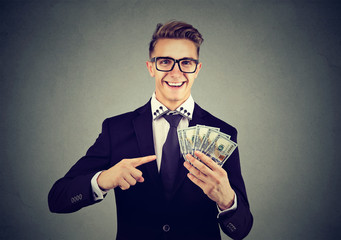 Successful young business man holding money dollar bills in hand isolated on gray background. Positive emotion facial expression. Financial reward concept