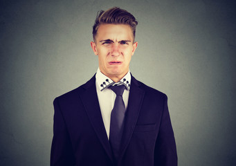 Portrait of a disgusted young business man isolated on gray wall background