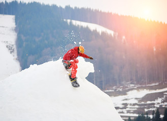 Male snowboarder riding from the top of the snowy hill with snowboard at winter ski resort. Skiing and snowboarding concept