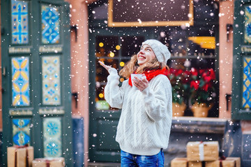 Young pretty woman near the shop with gifts enjoying winter, drinking coffe from the cup and looking up on falling snow. Girl dressed in warm white hat, red scarf and mittens.