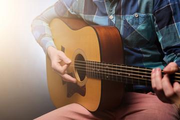 Musican with guitar in hand on dark background. Studio shot