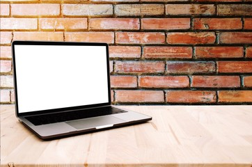laptop notebook computer with white blank screen on desk with old vintage brick wall, advertisement, workspace, internet technology, business and home office concept