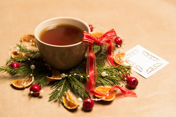 Cup of black tea, Christmas toys, gifts and decorations on craft background