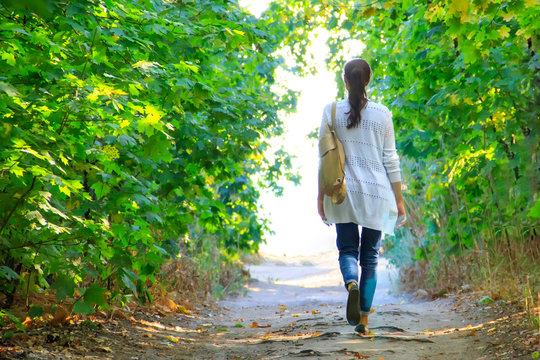 The girl walks along the path in the woods to the light in a white jacket and jeans.