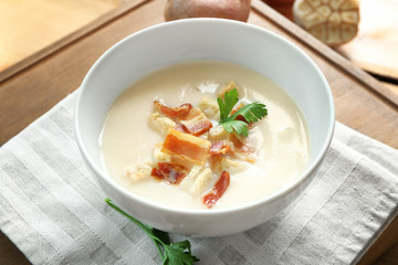 Bowl of yummy potato soup with bacon on wooden table