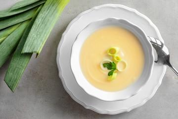 Bowl of yummy potato soup with leek on table
