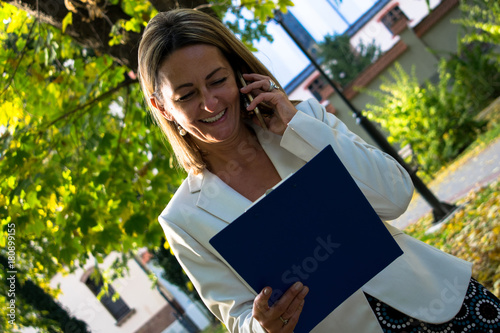 Happy Businesswoman Talking On Cell Phone While Reading