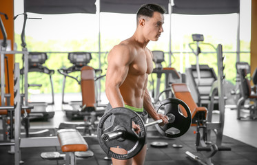 Muscular man training with barbell in gym