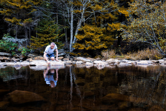 Young man looking into reflection of dark water touching with hand on peaceful, calm Red Creek river in Dolly Sods, West Virginia