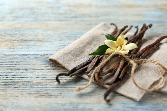 Dried vanilla pods and flower on wooden background