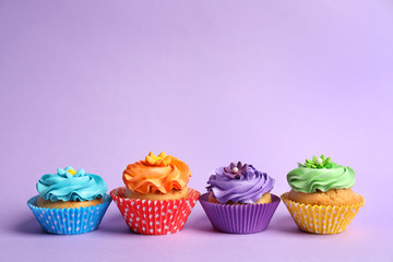 Tasty colorful cupcakes on color background
