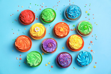 Tasty cupcakes on color background