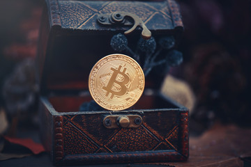 Golden bitcoin. Treasures - crypto currency mysterious. Old wooden box Virtual money on a dark background. warm toning