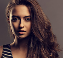 Beautiful calm woman with nude day makeup and effect eye brows, curly volume hair style looking mysteriously. Closeup toned vintage portrait