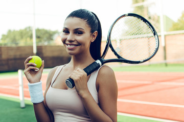 Tennis professional beauty. Beautiful young woman holding tennis racket and looking at camera with smile while standing on the tennis court.