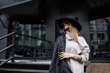 portrait of a young beautiful fashionable woman wearing sunglasses. A model in a stylish wide-brimmed hat. Harmoniously similar clothes in gray tones. Uleach style of shooting. Women's fashion. Wall mural
