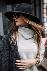 portrait of a young beautiful fashionable woman wearing sunglasses. A model in a stylish wide-brimmed hat. Harmoniously similar clothes in gray tones. Uleach style of shooting. Women's fashion.