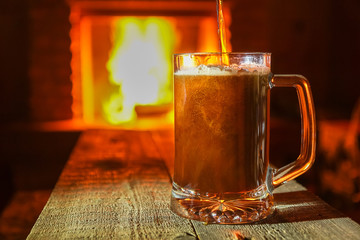 Beer pouring to the mug, on wooden table, against fireplace background,close up.