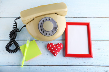 Beige retro telephone with photo frame and sticky notes on white wooden table