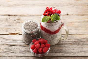 Chia pudding with berries in glass jar on wooden table
