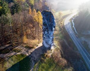 "Fototapeta Limestone monadnock, rock called ""Maczuga Herkuklesa"" (Hercules cudgel or bludgeon) in Pieskowa Skala near Krakow in Poland. Aerial view in fall, in sunrise light through the morning fog obraz"