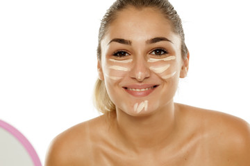 A young woman concealer a corrector under the eyes