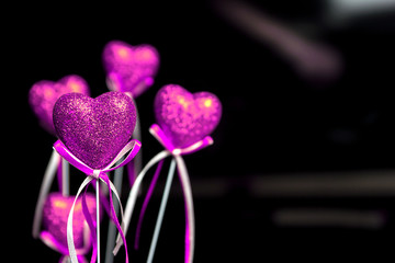 Valentines day. Pink hearts on black blurred background close-up with copy space for congratulation