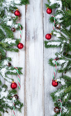 Vertical borders of snowy Christmas red ornaments and candy canes hanging in evergreen tree branches