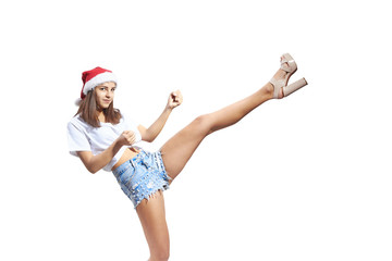 In a Santa Claus hat, a girl beats a kick leg isolated