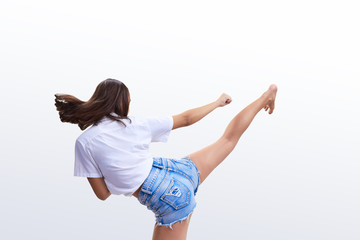 On a light background a girl in shorts beats a kick