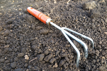 Garden hand flower rake in the loosen soil in the garden