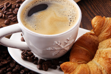 coffee and croissant with coffee beans. breakfast energy concept.